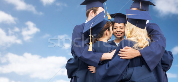 happy students or bachelors hugging over blue sky Stock photo © dolgachov