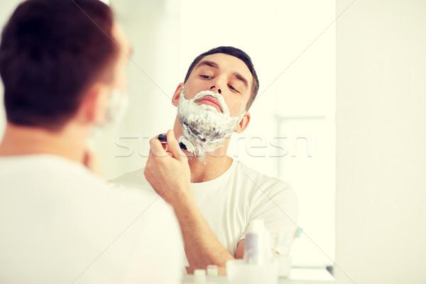 man shaving beard with razor blade at bathroom Stock photo © dolgachov
