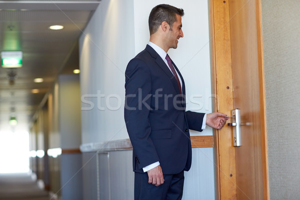businessman with keycard at hotel or office door Stock photo © dolgachov