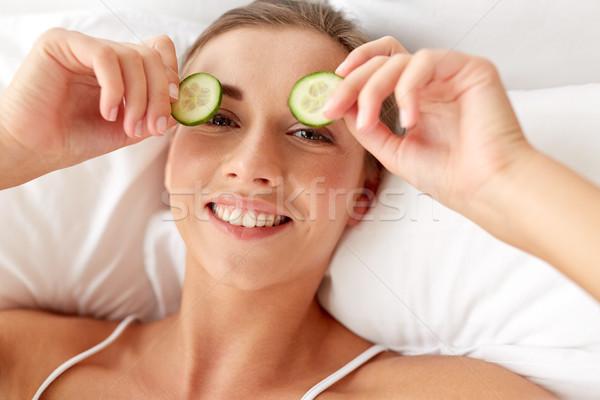 beautiful woman applying cucumbers to eyes at home Stock photo © dolgachov