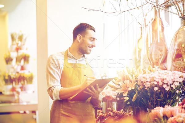 Fleuriste homme presse-papiers personnes vente Photo stock © dolgachov