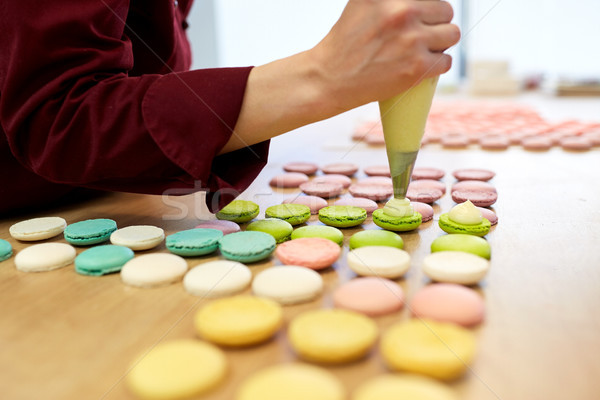 chef with injector squeezing filling to macarons Stock photo © dolgachov