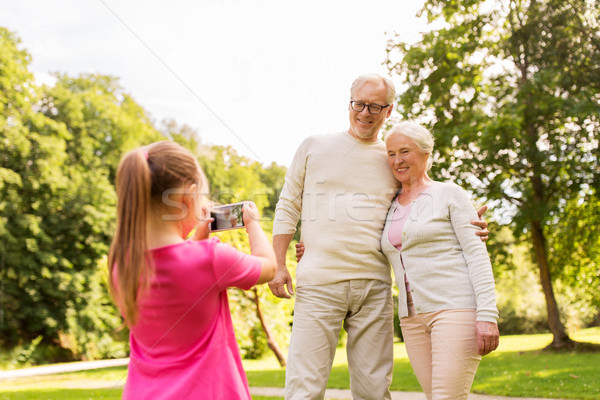 granddaughter photographing grandparents at park Stock photo © dolgachov