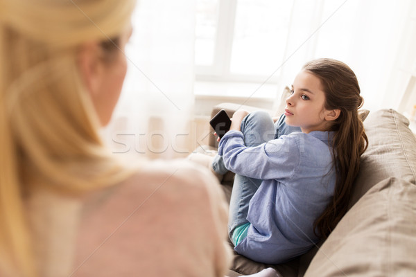 sad girl with smartphone looking at mother at home Stock photo © dolgachov