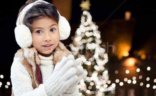 happy girl wearing earmuffs over christmas lights Stock photo © dolgachov