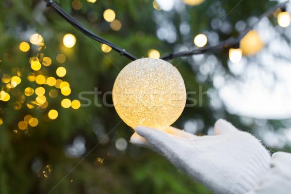 close up of hand with christmas tree garland bulb Stock photo © dolgachov