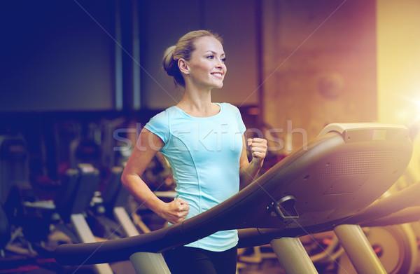 smiling woman exercising on treadmill in gym Stock photo © dolgachov