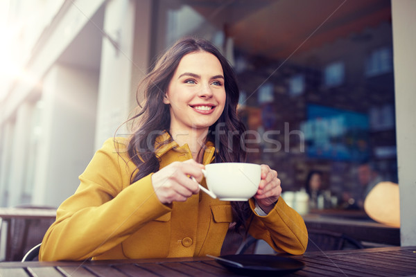 Stock photo: happy woman drinking cocoa at city street cafe