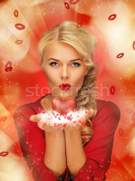 woman blowing kisses on the palms of her hands Stock photo © dolgachov