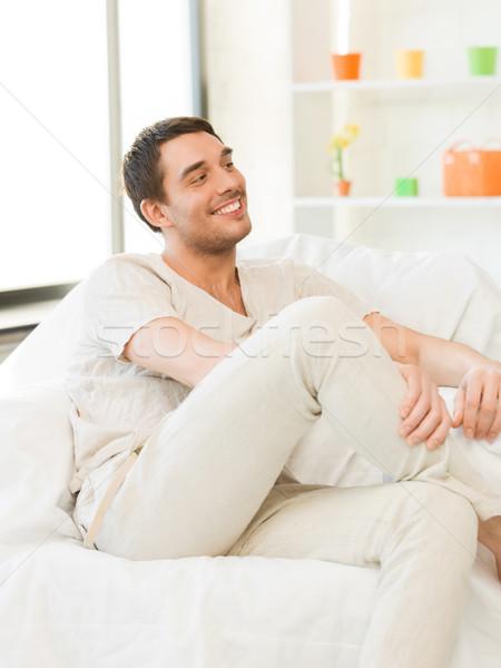 Yakışıklı adam oturma kanepe resim adam mutlu Stok fotoğraf © dolgachov