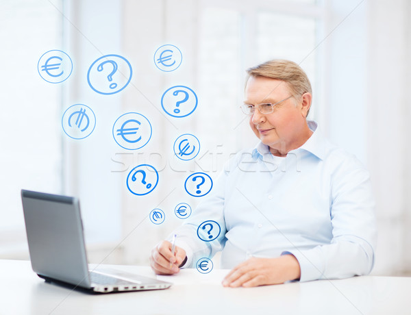 Stock photo: old man in eyeglasses filling a form at home