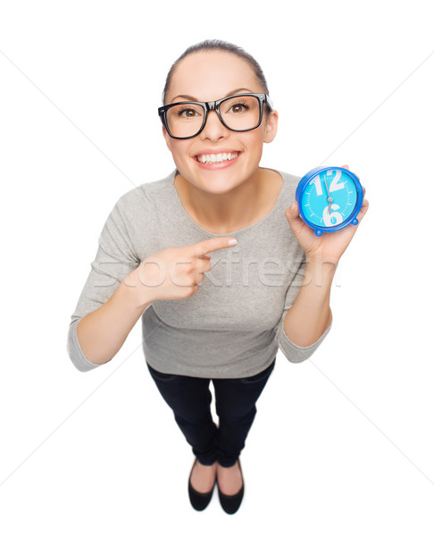 woman in eyeglasses pointing finger to blue clock Stock photo © dolgachov