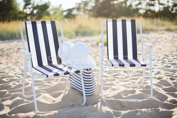 two beach lounges with beach bag and white hat Stock photo © dolgachov