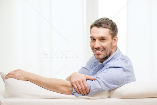 smiling man sitting on sofa at home Stock photo © dolgachov