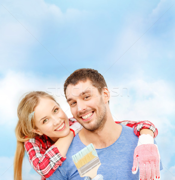 Stock photo: smiling couple covered with paint with paint brush