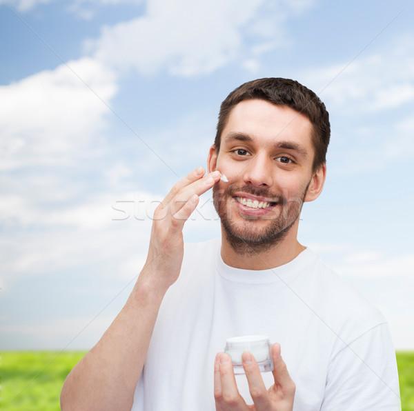 Belo sorridente homem creme saúde beleza Foto stock © dolgachov