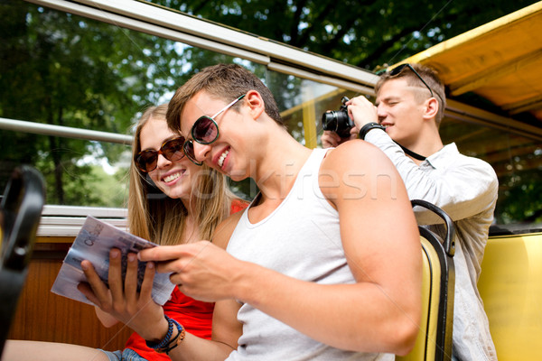 smiling couple with book traveling by tour bus Stock photo © dolgachov