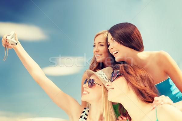smiling girls taking photo in cafe on the beach Stock photo © dolgachov