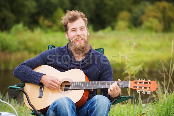 smiling man playing guitar in camping Stock photo © dolgachov