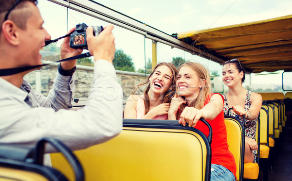 laughing friends with camera traveling by tour bus Stock photo © dolgachov