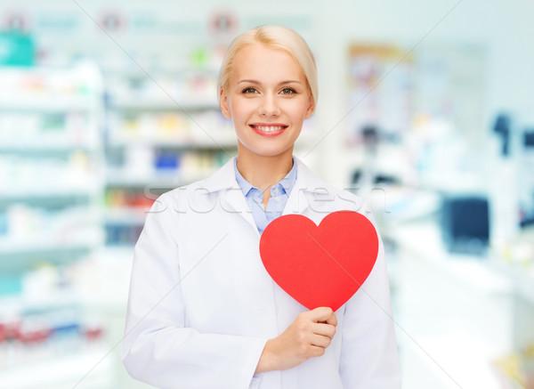 woman pharmacist with heart at drugstore Stock photo © dolgachov