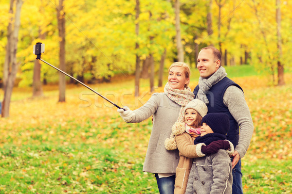 happy family with smartphone and monopod in park Stock photo © dolgachov