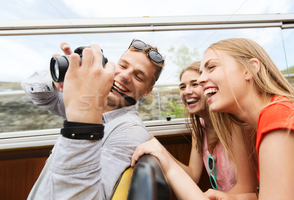 happy friends with camera traveling by tour bus Stock photo © dolgachov