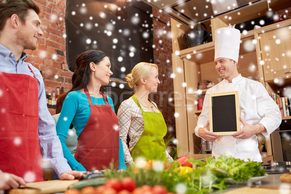 happy friends and chef cook with menu in kitchen Stock photo © dolgachov