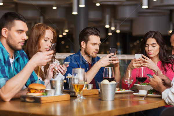 friends with smartphones dining at restaurant Stock photo © dolgachov