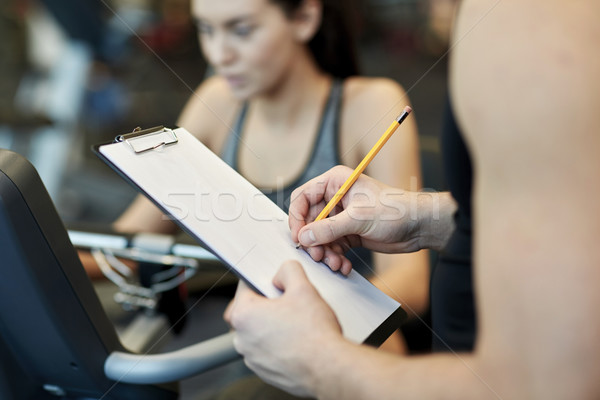 close up of trainer hands with clipboard in gym Stock photo © dolgachov