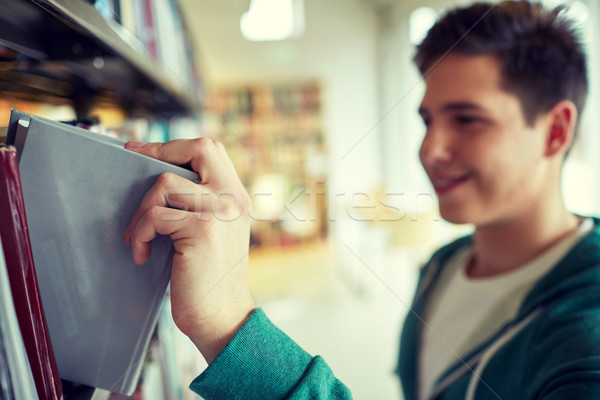 close up of happy student boy with book in library Stock photo © dolgachov
