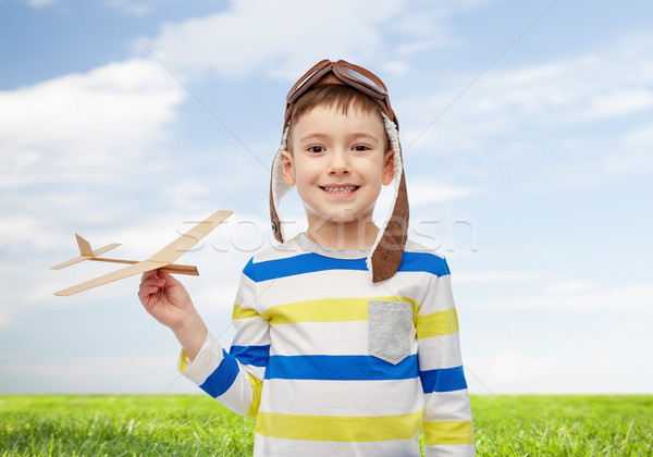happy little boy in aviator hat with airplane Stock photo © dolgachov