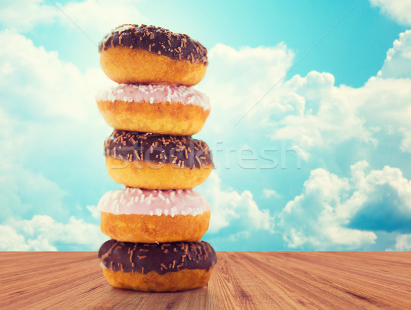 Stock photo: close up of glazed donuts pile over blue sky