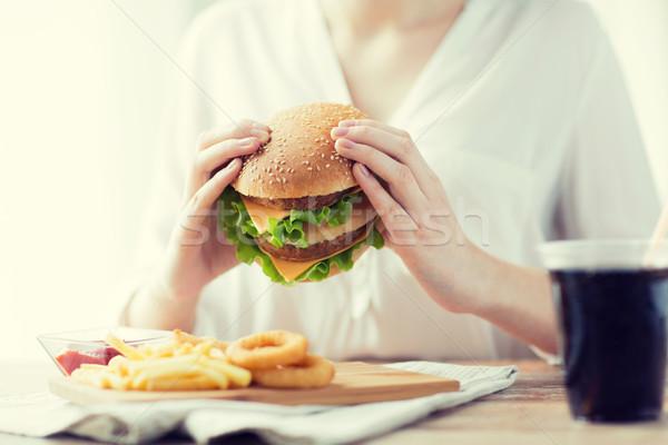 Közelkép nő kezek tart hamburger gyorsételek Stock fotó © dolgachov
