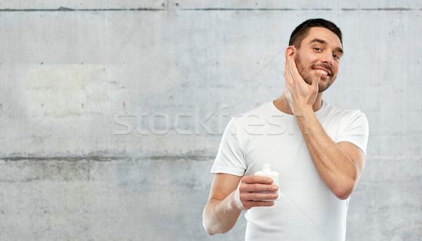 Szczęśliwy młody człowiek krem mleczko kosmetyczne twarz Zdjęcia stock © dolgachov