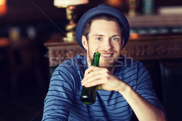 happy young man drinking beer at bar or pub Stock photo © dolgachov