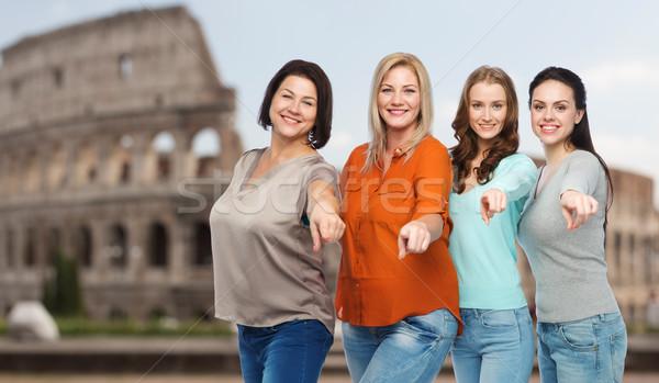 group of happy women pointing finger over coliseum Stock photo © dolgachov