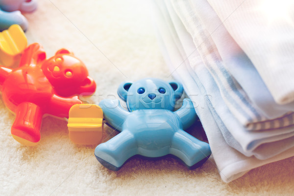 close up of baby rattle and clothes for newborn Stock photo © dolgachov