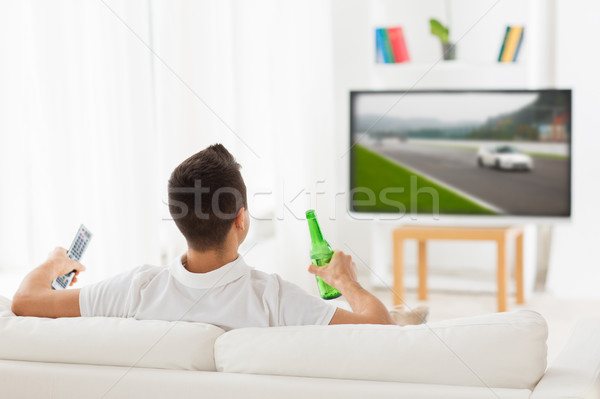 man watching tv and drinking beer at home Stock photo © dolgachov