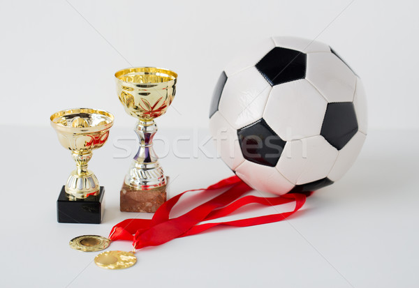 close up of football ball, golden cups and medals Stock photo © dolgachov