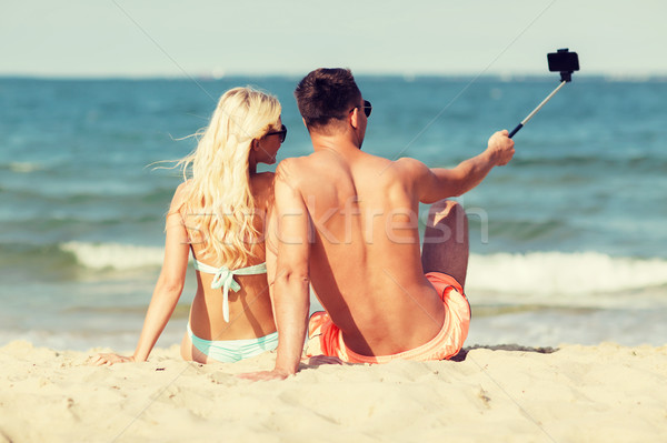 happy couple in swimwear sitting on summer beach Stock photo © dolgachov