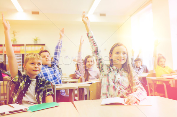 group of school kids raising hands in classroom Stock photo © dolgachov