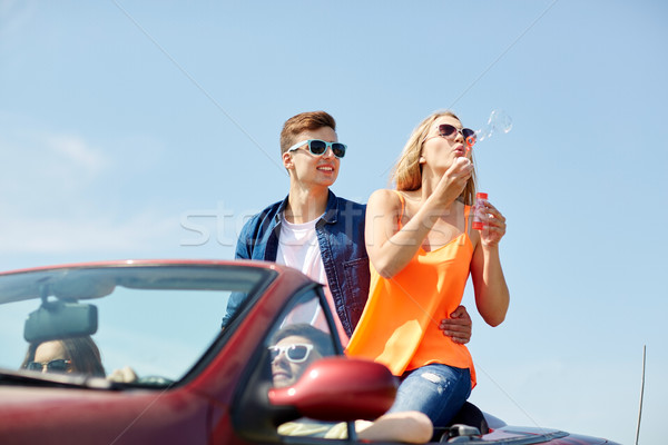 friends driving in car and blowing bubbles Stock photo © dolgachov