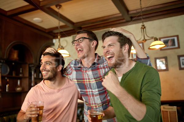 friends with beer watching sport at bar or pub Stock photo © dolgachov