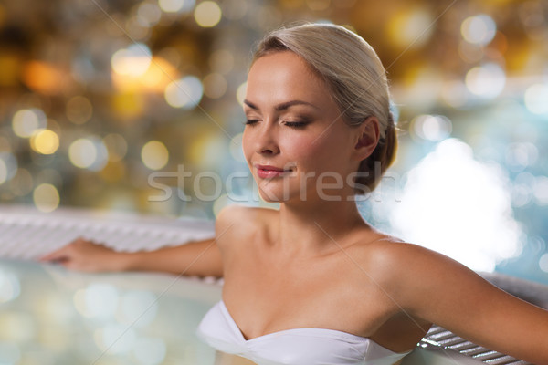 happy womani sitting in jacuzzi at poolside Stock photo © dolgachov