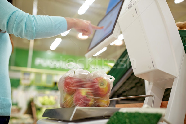 woman weighing apples on scale at grocery store Stock photo © dolgachov