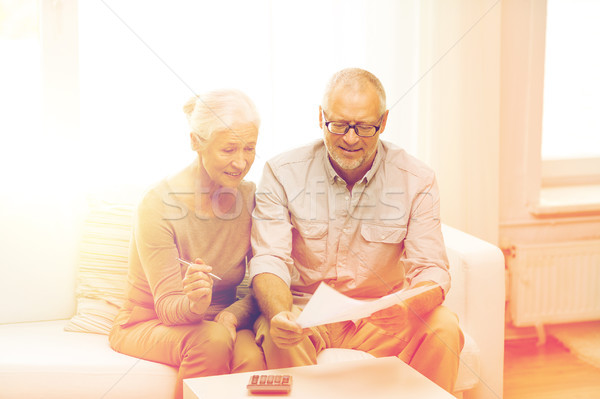 senior couple with papers and calculator at home Stock photo © dolgachov