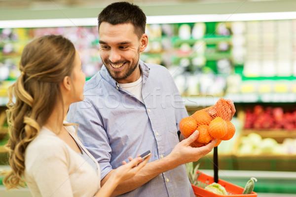 Boldog pár vásárol narancsok élelmiszerbolt vásárlás Stock fotó © dolgachov