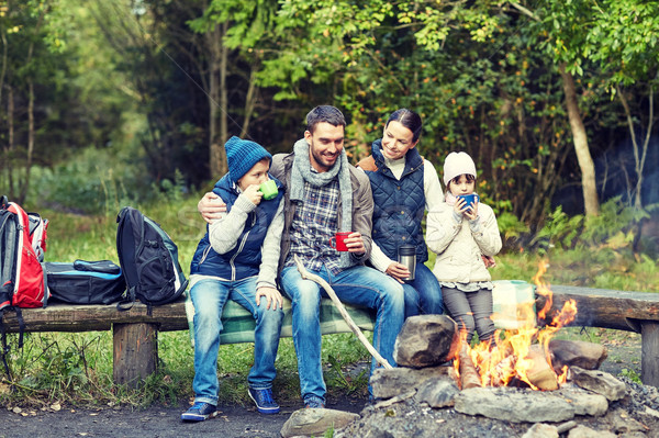 happy family sitting on bench at camp fire Stock photo © dolgachov