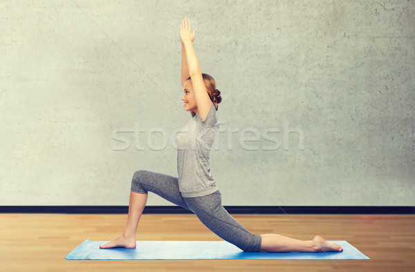 happy woman making yoga in low lunge on mat Stock photo © dolgachov